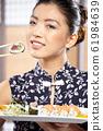 beautiful asian woman eating sushi with chopsticks 61984639