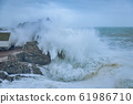 Big waves on the ocean in a cloudy cold winter 61986710