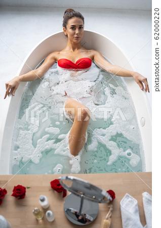 Serene pretty female taking a relaxing bath 62000220