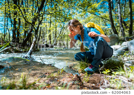 Woman refreshing herself with fresh water from creek while hiking 62004063
