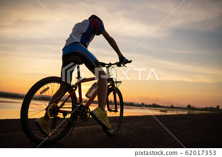Men cycling bicycle on the road in the sunset time 62017353