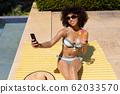 Young woman taking selfie near swimming pool 62033570