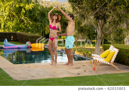 Happy young couple relaxing near the swimming pool 62033801