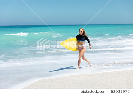 Young woman running with surboard 62033976