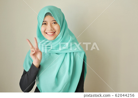 woman pointing number 2 up, victory hand gesture 62044256