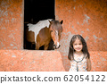 a girl with Horse in a stable 62054122