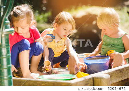 Group of girl children playing in the sandbox 62054673