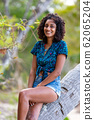 Lovely smiling young woman sitting on palm tree 62065204