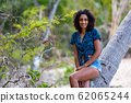 Lovely young African woman sitting on palm tree 62065244