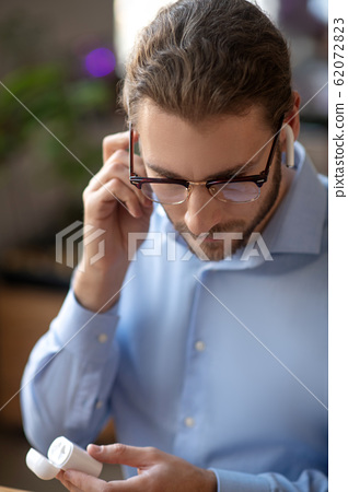 Serious young man with glasses and wireless headphones. 62072823