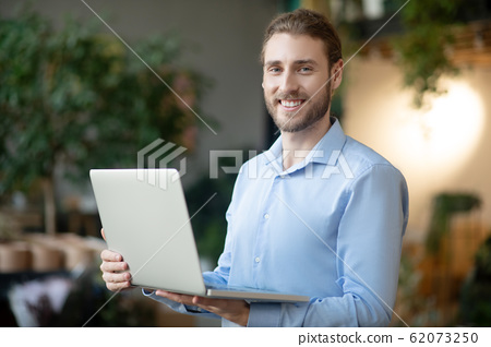 Young smiling man with a laptop in his hands. 62073250