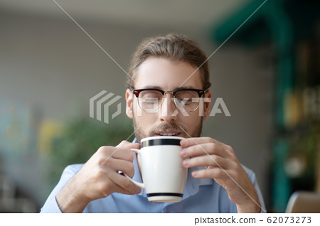 Young man with glasses looking smiling at a cup of coffee. 62073273