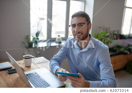 Young man sitting at laptop with tablet in his hands. 62073314
