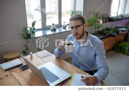 Young man sitting at a table in the office drinking coffee. 62073315