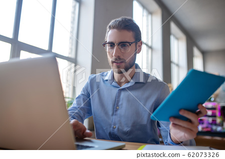 Young man in glasses with tablet in hand looking at laptop 62073326