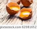 Broken chicken eggs with yolk on wooden table 62081652