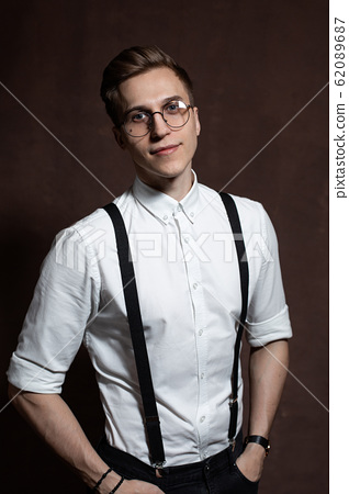 Man in round glasses, suspenders and a white shirt. 62089687