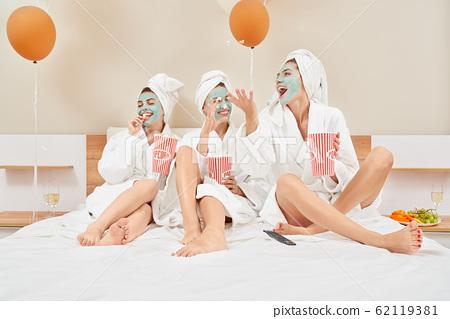 Girls eating popcorn in bed, having fun. 62119381