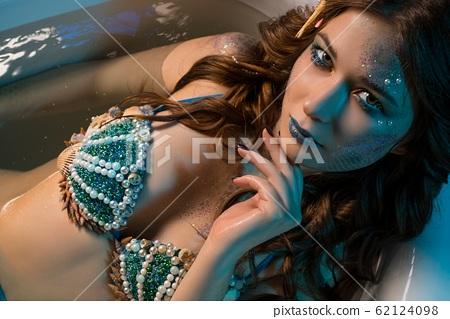 Woman in mermaid image lying in bath shot 62124098