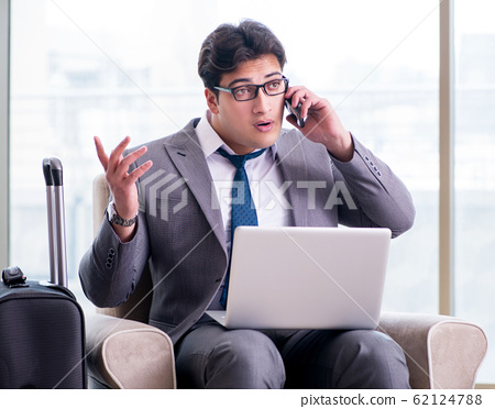 Young businessman in airport business lounge waiting for flight 62124788