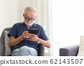 elder gray beard white hair with glasses looking attention at his smartphone 62143507