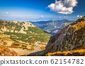 Mountainous landscape with hills and valleys. 62154782