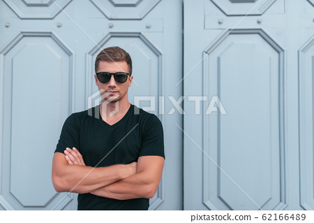 man in black T-shirt and sun goggles, in summer in city background of wooden doors, posing, fashion and modern style, free space for copy text. Emotions of positive and self-confidence. 62166489