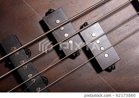 Bass electric guitar with four strings closeup.