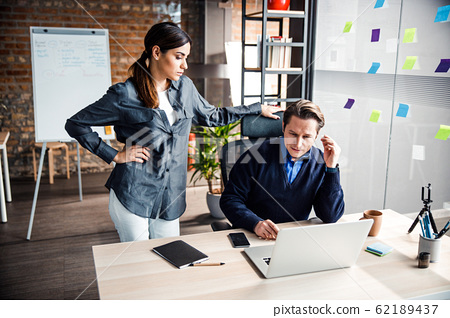 Attentive office worker listening to her colleague 62189437