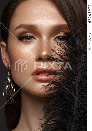 A beautiful girl with evening make-up, a Hollywood wave and a black feather in her hand. Beauty face. 62205979