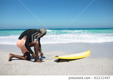 Old man with a surfboard at the beach 62211497