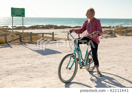 Old man with a bike at the beach 62211641