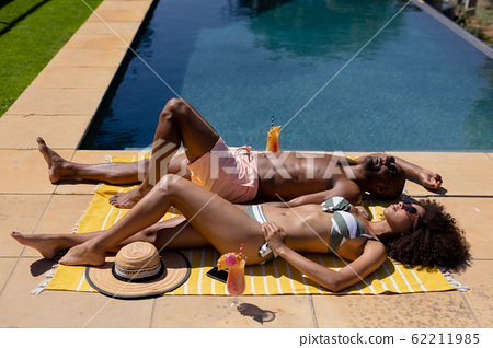 Young couple relaxing near swimming pool on a sunny day 62211985