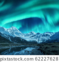 Aurora borealis over the snowy mountains, coast of the lake and reflection in water 62227628