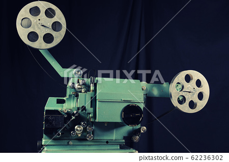 Old film projector on a black background 62236302