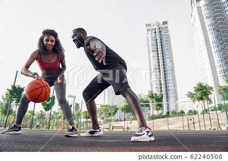 Outdoors Activity. African couple on basketball court girl dribbling while guy blocking smiling happy 62240508