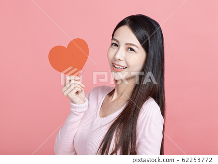 Happy young woman  holding red paper hearts  and 62253772