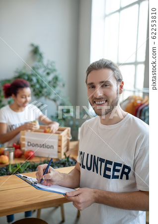 Young bearded man in a white T-shirt with a folder. 62253810