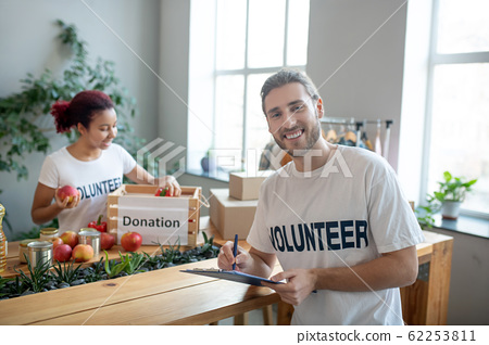Young man with folder, girl putting fruits in a box. 62253811