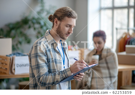 Young busy man standing indoors at work and writing. 62253859