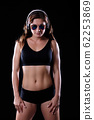 Sporty female girl showing off her perfect body on black background 62253869