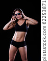 Sporty female girl showing off her perfect body on black background 62253871