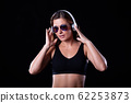 Sporty female girl showing off her perfect body on black background 62253873