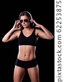 Sporty female girl showing off her perfect body on black background 62253875