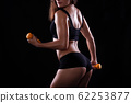 Fitness girl with dumbbells on a dark background 62253877