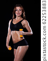 Fitness girl with dumbbells on a dark background 62253883