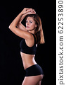 Sporty female girl showing off her perfect body on black background 62253890