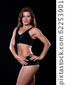Sporty female girl showing off her perfect body on black background 62253901