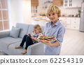 Boy standing with plate of biscuits, girl sitting on sofa 62254319