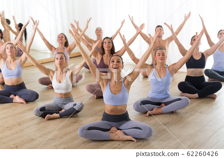 Group of young sporty attractive people in yoga studio, practicing yoga lesson with instructor, sitting on floor in Padmasana, lotus meditative yoga pose. Healthy active lifestyle, working out in gym 62260426